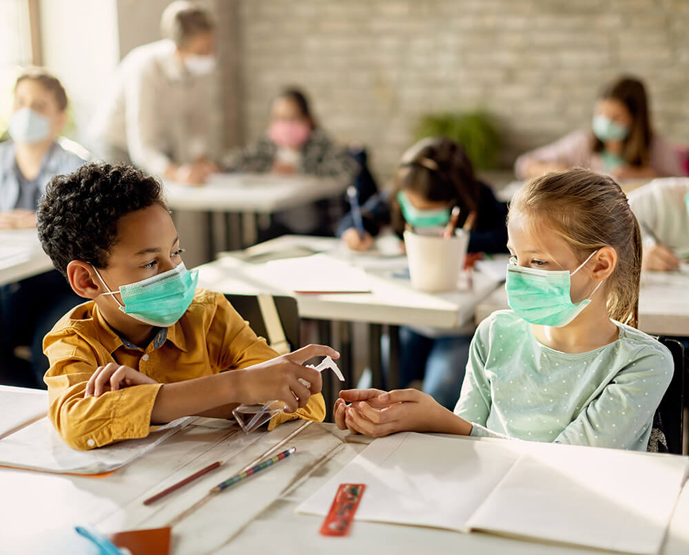 Kids in the classroom sharing hand sanitizer.